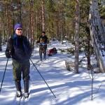 Kaksi hiihtäjää lumisessa metsässä.