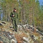 Metsästäjä aurinkoisessa rinteessä.